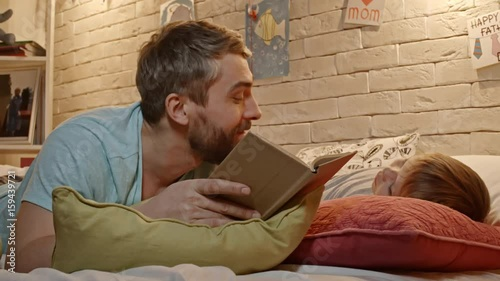 Happy father lying on bed with little son, reading him fairytale for good night and smiling