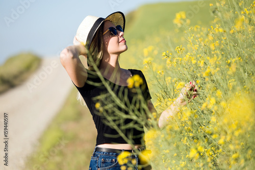 Beautiful young woman with flowers enjoying summer in a field. - 159440597