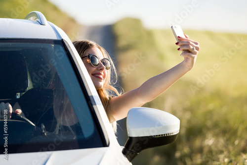 Poster Beautiful young woman taking a selfie in a car parked in the field