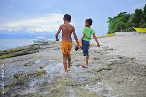 Póster two little asian boys splashing their feet in shallow water ahead of oncoming wa
