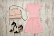 Pink dress, black shoes and a beige bag. Fashionable concept