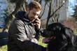 Young man with the Newfoundland dog using mobile device