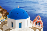 The Greek Orthodox Church on the background waters of the Aegean sea in Oia town on Santorini island in Greece