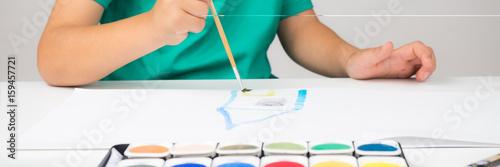 kind malt mit einem pinsel auf einem blatt papier