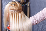 Fototapety Hair extensions procedure. Hairdresser does hair extensions to young girl, blonde in a beauty salon. Selective focus.