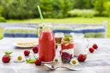 Delicious strawberry smoothie on the wooden table in the garden.