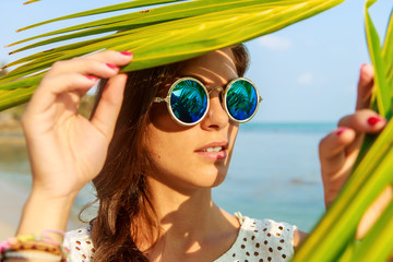 Close up portrait of a beautiful slim woman in fashion round sunglasses and white shirt push through palm leaves to the sun. Beauty sunshine cute girl on a sand beach with large stone.