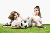 Girl and boy are lying on the grass with a soccer ball. Two children soccer players in sports smile before the game. White background
