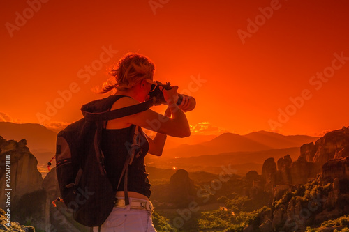 Fotobehang Rood Traveler woman photographer with telelens takes photos of rock monasteries Meteora, Central Greece, Europe. Female photographer takes picture outdoors. Sunset light. Scenic travel destination.