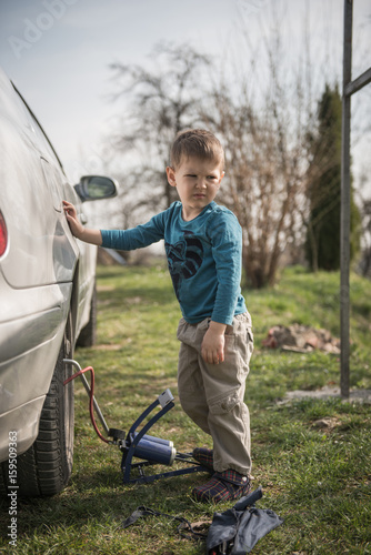 Little boy leaning against car standing next to pump in nature