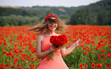 young beautiful girl in a red skirt and white blouse on the background of beautiful field with poppies in summer