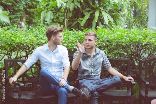Two friends men talking sitting in a garden.