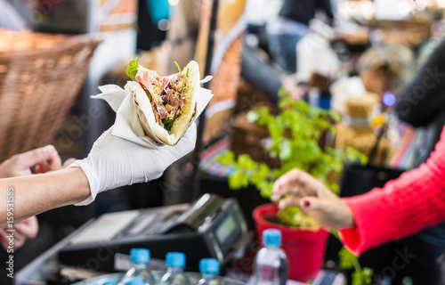Chef handing a tortilla to a foodie at a street food market