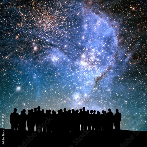 Fototapeta group of silhouetted people and lights of universe