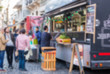 People at a street food market festival on a sunny day, blurred on purpose
