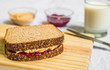 Peanut butter and jelly sandwich on a wooden board against white background
