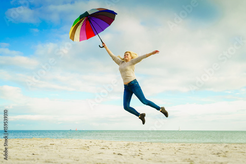 Póster Woman jumping with colorful umbrella on beach