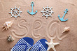 Word Sea drawn on beach sand with anchor and ship wheel