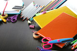 Different school supplies on dark wooden table