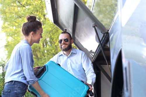 Fototapeta Pasażerka wkłada walizkę do luku bagażowego w autobusie.