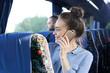 Podróż autokarem turystycznym. Pasażer rozmawia przez telefon w czasie podróży.