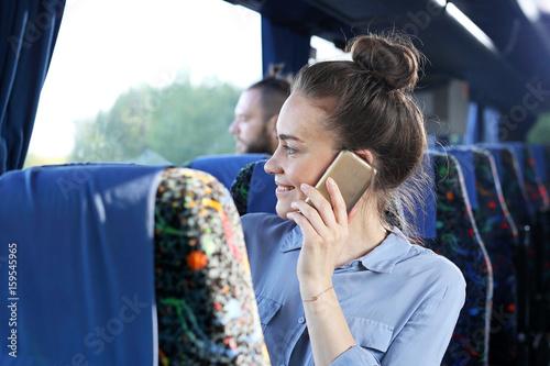 Fototapeta Podróż autokarem turystycznym. Pasażer rozmawia przez telefon w czasie podróży.