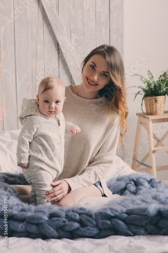 Deurstickers Franse bulldog happy mother and 8 month old baby playing and relaxing at home in bedroom in the morning. Cozy family lifestyle in modern scandinavian interior.