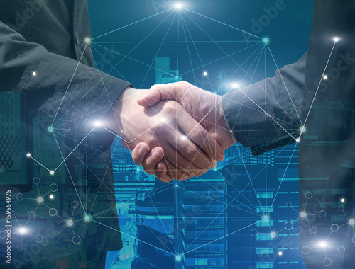 Foto Murales handshake of businessman with the futuristic network connection technology on cityscape background, double exposure, business technology and Social Network concept