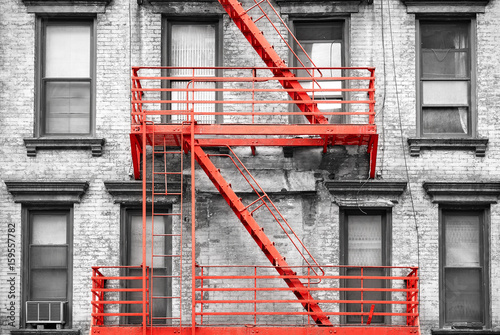 Red fire escape at black and white filtered residential building, New York City, USA.