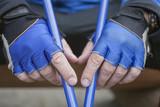 мужские руки в спортивных перчатках и с палками для скандинавской ходьбы