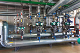 The interior of a modern gas boiler house with pumps, valves, a multitude of sensors and barrels - 159575729