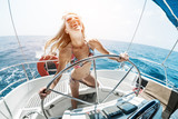 Young happy woman steering sailing boat in a tropical sea
