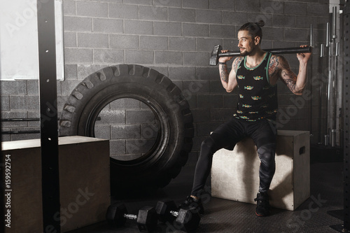 crossfit man sits in a gym with a sports hammer on his shoulders