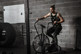 Fototapety young man using exercise bike at the gym. Fitness male using air bike for cardio workout at crossfit gym.