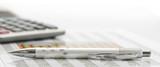 Kugelschreiber und Taschenrechner auf Zahlentabelle