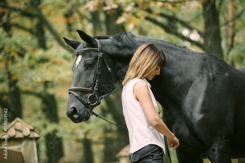 Portrait of young woman and black horse in a forest.