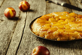 Tarte tatin upside down peach tart on vintage rustic wooden table. Summer baking. French cuisine. Selective focus. Toned image  - 159613318