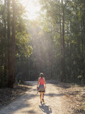 Australia, New South Wales, Port Macquarie, Rear view of mature woman walking along dirt road in forest - 159625727