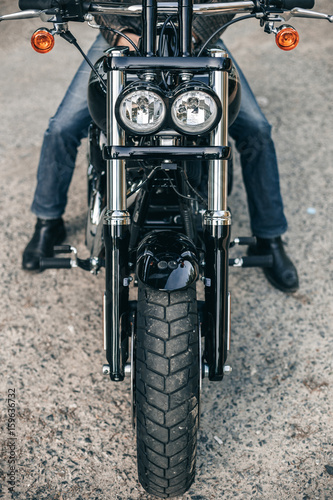 Motorcycle headlight and man wearing jeans on motorbike Poster
