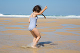 little girl in summer vacation play and jump in sand beach