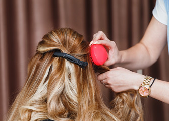 Hairdresser combing woman's hair at beauty salon