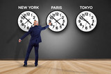Businessman in front of a wallwith clocks of different country - Jetlag concept