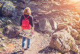 Woman with a red backpack walking along a path in the mountains