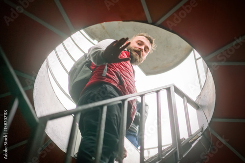 Man in a red vest and backpack climbs the stairs in a round tower Poster
