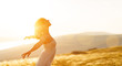 Leinwanddruck Bild - Happy woman standing with her back on sunset in nature iwith open hands