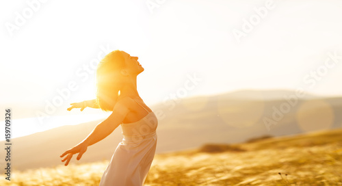 Leinwanddruck Bild Happy woman standing with her back on sunset in nature iwith open hands