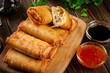 Spring rolls with chicken and vegetables on chopping board