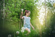 The child girl collects fluffy white dandelions in the tall grass. - 159716934
