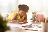 Concentrated toddler in yellow dress coloring picture with pencils while lying on floor, blurred background - 159720760