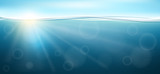 Underwater horizontal banner in sea with sunlight shining under. Blue sky and sun on top, vector illustration for water design